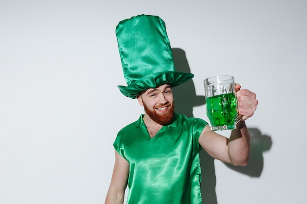 Szczęśliwy brodaty mężczyzna w zielonej kostiumowej trzyma filiżance