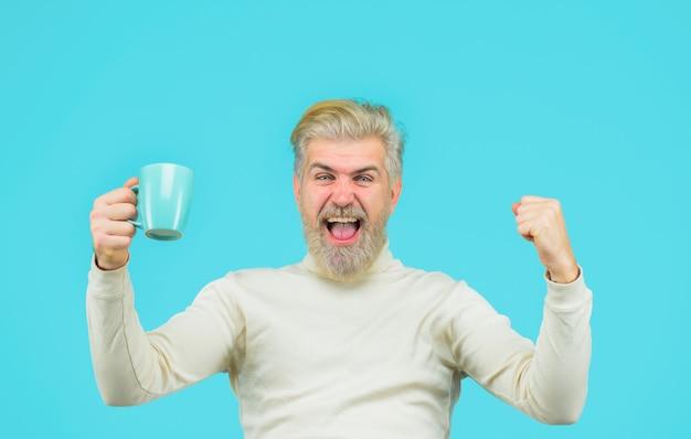 Szczęśliwy brodaty mężczyzna z filiżanką mężczyzna pijący gorącą kawę w kawiarni modny mężczyzna ze stylowymi włosami z