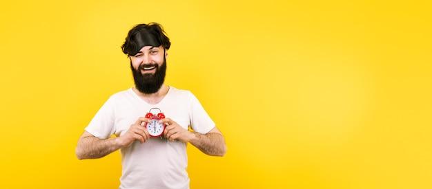 Szczęśliwy brodaty mężczyzna z maską snu i budzikiem na żółtym tle, koncepcja dzień dobry