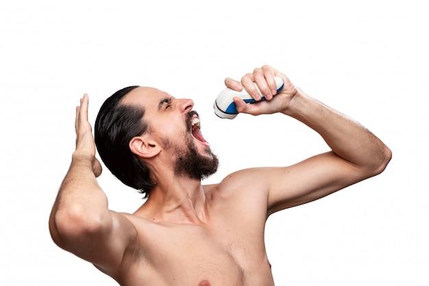 Szczęśliwy brodaty mężczyzna z wąsami używa golarki elektrycznej jako nagiej stojącej mikrofonu. ciesząc się poranną rutyną i goleniem.