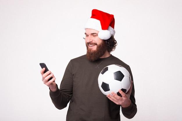 Szczęśliwy brodaty mężczyzna za pomocą swojego smartfona i trzymając piłkę nożną