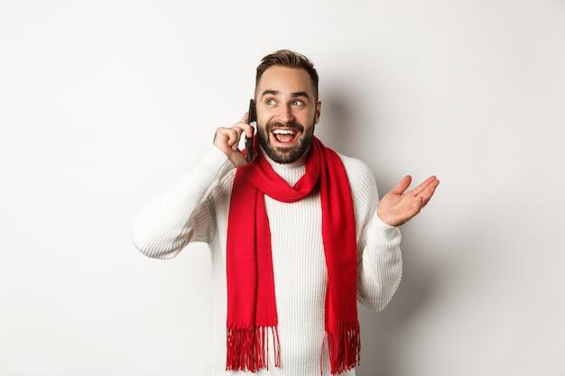 Szczęśliwy brodaty mężczyzna życzy wesołych świąt na telefonie, dzwoniąc do kogoś i rozmawiając, stojąc w swetrze z czerwonym szalikiem, białe tło.