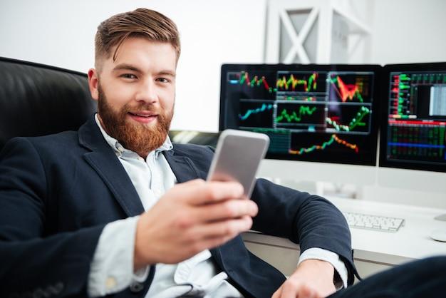 Szczęśliwy brodaty młody biznesmen siedzi i używa telefonu komórkowego w biurze