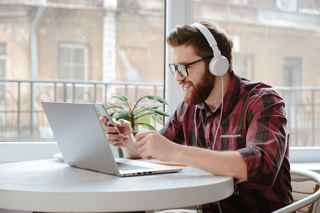 Szczęśliwy brodaty młody człowiek używa wiszącą ozdobę i słuchającą muzykę.