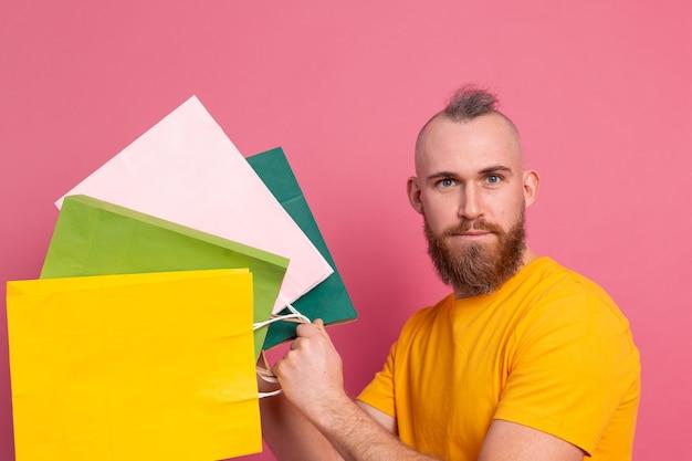 Szczęśliwy brodaty pozytywny mężczyzna dorywczo wygląd z kolorowe torby na zakupy studio różowym tle