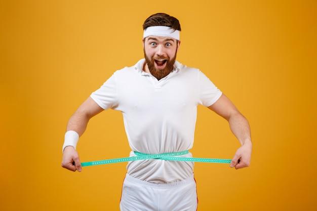 Szczęśliwy brodaty sprawność fizyczna mężczyzna mierzy jego talię z taśmą