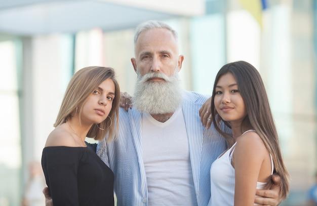 Szczęśliwy brodaty starszy mężczyzna ściska jego młodych przyjaciół.