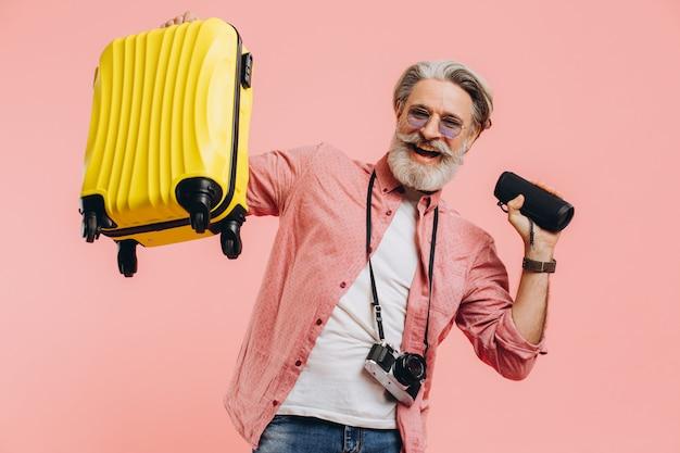 Szczęśliwy brodaty stylowy mężczyzna w okularach przeciwsłonecznych z kamerą trzyma walizkę i przenośny głośnik
