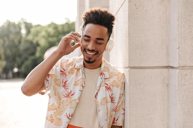 Szczęśliwy brunet ciemnoskóry mężczyzna w kwiecistej koszuli uśmiecha się z zamkniętymi oczami