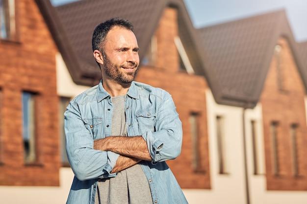Szczęśliwy brunetka mężczyzna pozuje przed nowo wybudowanym domem