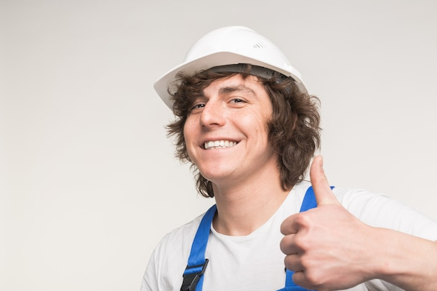 Szczęśliwy budowniczy mężczyzna śmiejąc się i robiąc kciuki do góry na białym tle