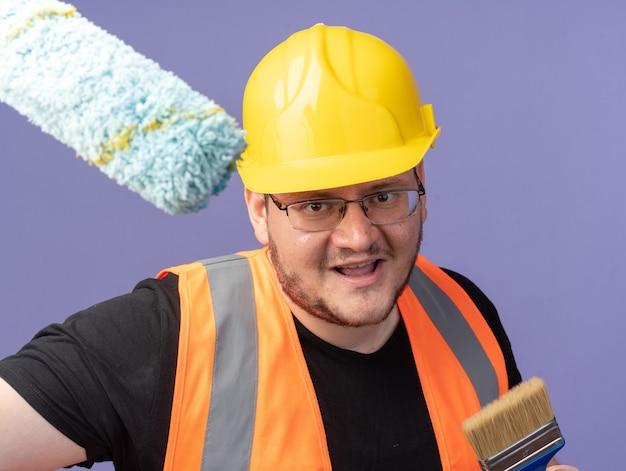 Szczęśliwy budowniczy mężczyzna w kamizelce budowlanej i kasku ochronnym, trzymający wałek i pędzel