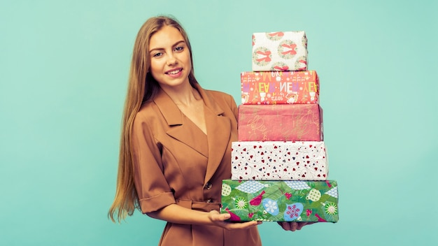 Szczęśliwy całkiem młoda kobieta trzyma pudełko na niebieskim tle. boże narodzenie i koncepcja nowego roku
