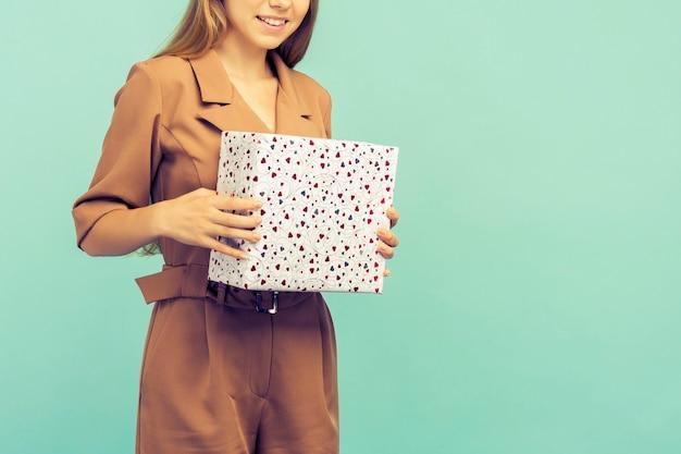 Szczęśliwy całkiem młoda kobieta trzyma pudełko na niebieskim tle.