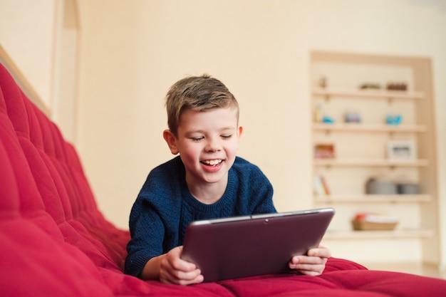 Szczęśliwy chłopak wathcing na ekranie tabletu i uśmiechnięty