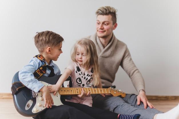 Szczęśliwy chłopak z gitarą ojca