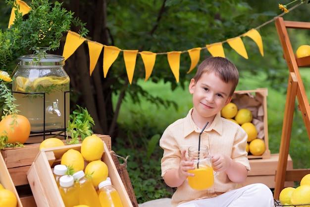 Szczęśliwy chłopczyk jedzenie cytryn i picie lemoniady na świeżym powietrzu w lecie