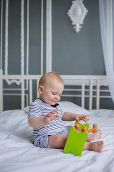 Szczęśliwy chłopczyk siedzi w pasiastym kombinezonie i bawi się drewnianą zabawką na białym łóżku w pokoju
