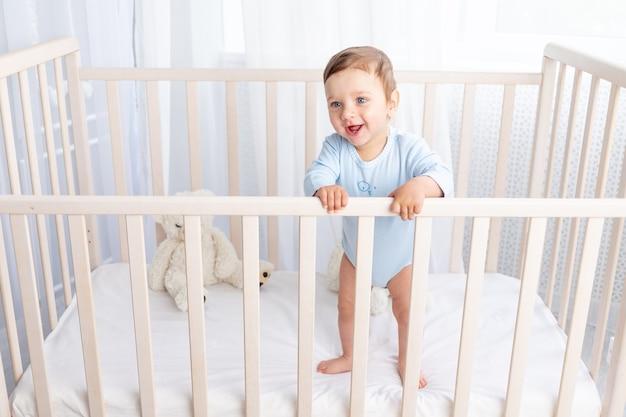 Szczęśliwy chłopczyk stoi w łóżeczku w przedszkolu i uśmiecha się lub śmieje
