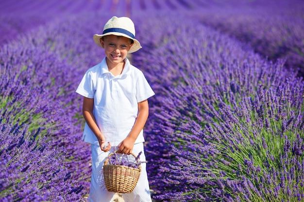 Szczęśliwy chłopczyk w kapeluszu z koszem w lawendowym polu latem w pobliżu valensole