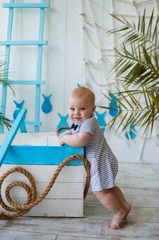 Szczęśliwy chłopczyk w pasiastym kombinezonie stoi w pobliżu drewnianej łodzi i patrzy w kamerę na murze