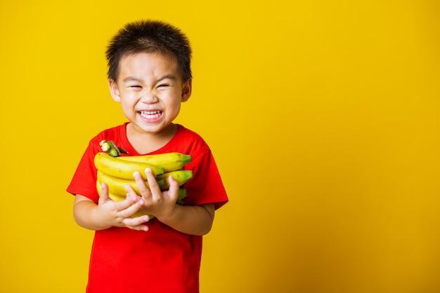 Szczęśliwy chłopiec azjatyckich dziecko uśmiech trzyma banany grzebień owoców