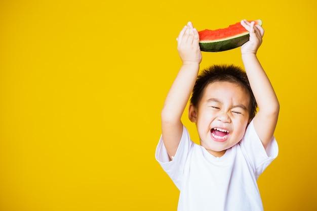 Szczęśliwy chłopiec azjatyckich dziecko uśmiech trzyma rżnięty arbuz świeży dla jedzenia