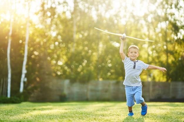 Szczęśliwy chłopiec bawi się bawiąc się dużym samolotem na zewnątrz