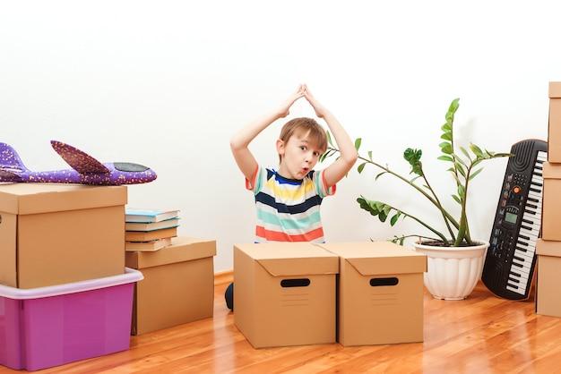 Szczęśliwy chłopiec bawi się podczas przeprowadzki do nowego domu. obudowa dla młodej rodziny z dziećmi. dziecko co dach ręce.