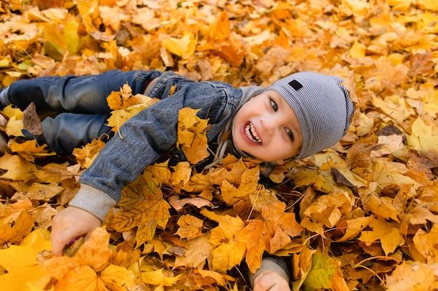 Szczęśliwy chłopiec bawi się w jesienne liście
