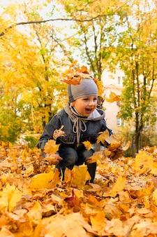 Szczęśliwy chłopiec bawi się w liściach jesienią