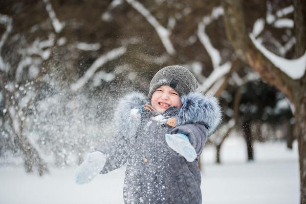 Szczęśliwy chłopiec bawi się w śniegu, zimowe gry
