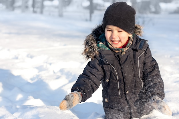 Szczęśliwy chłopiec bawi się w śniegu