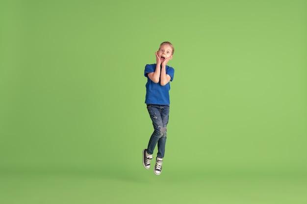 Szczęśliwy chłopiec bawiący się i bawiący się emocjami na zielonej ścianie