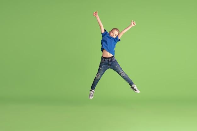 Szczęśliwy chłopiec bawiący się i bawiący się na zielonym tle studia, emocje