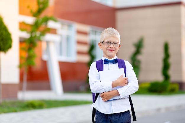 Szczęśliwy chłopiec blond uczeń w okularach z plecakiem stoi w szkole i się śmieje