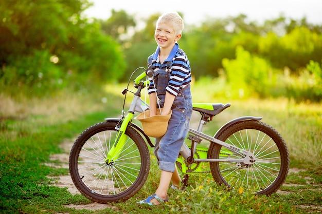 Szczęśliwy chłopiec blond z rowerem stoi w polu latem