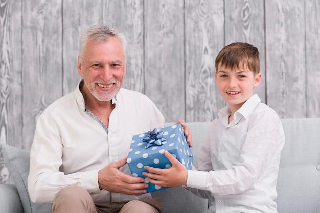 Szczęśliwy chłopiec daje prezentowi urodzinowemu jego dziadkowi