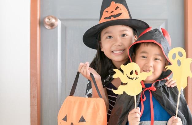 Szczęśliwy chłopiec diabeł uśmiech i urocza mała czarownica