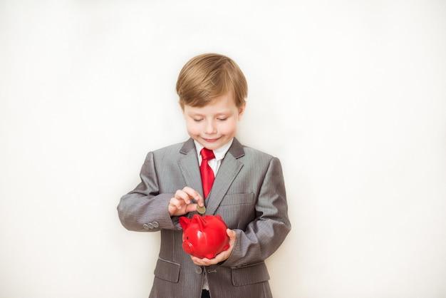 Szczęśliwy chłopiec dziecko stoi w modnym garniturze z skarbonką w rękach. sukces, kreatywna i innowacyjna koncepcja biznesowa