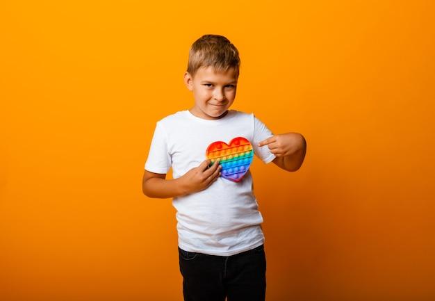 Szczęśliwy chłopiec gospodarstwa pop to gra w ręce, na białym tle na żółtym tle. wesoły dzieciak z pop it