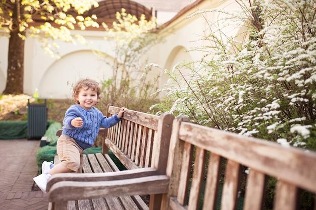 Szczęśliwy chłopiec gra i bieganie w parku wiosną. małe uśmiechnięte dziecko bawić się w parku miejskim.