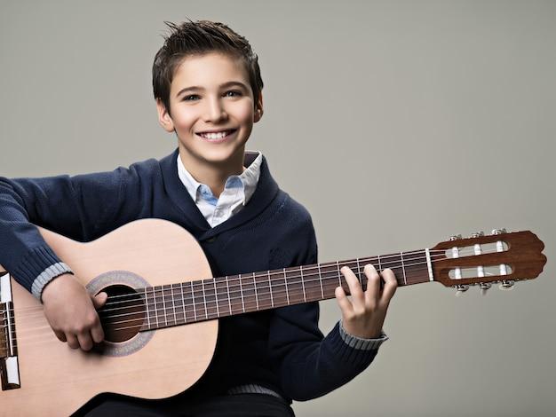 Szczęśliwy chłopiec gra na gitarze akustycznej.