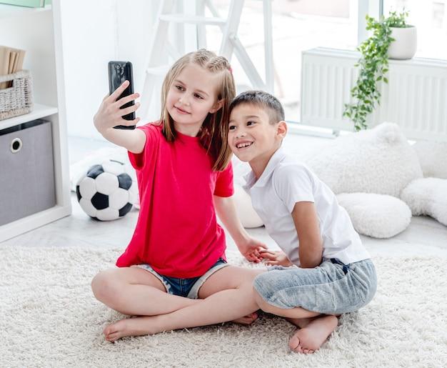 Szczęśliwy chłopiec i dziewczynka przy selfie