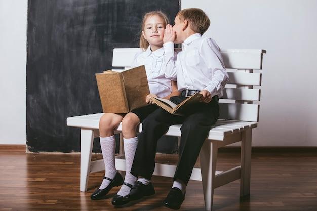 Szczęśliwy chłopiec i dziewczynka z klasy szkoły podstawowej na ławce czytają książki na tle łupków