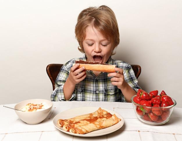 Szczęśliwy chłopiec je chleb z czekoladą