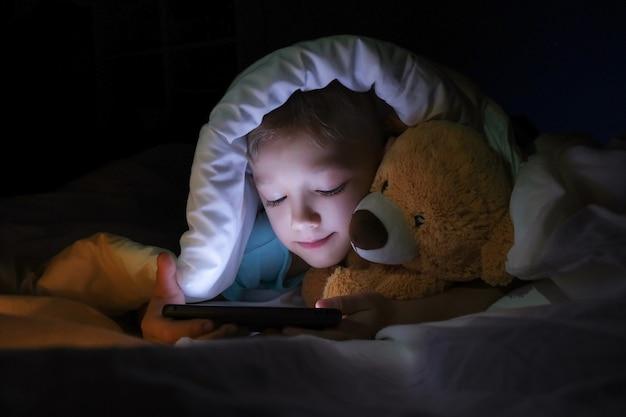Szczęśliwy chłopiec leży z misiem zabawka w łóżku pod kocem i za pomocą urządzenia smartphone cyfrowy tablet w ciemności. twarz dziecka oświetla jasny monitor