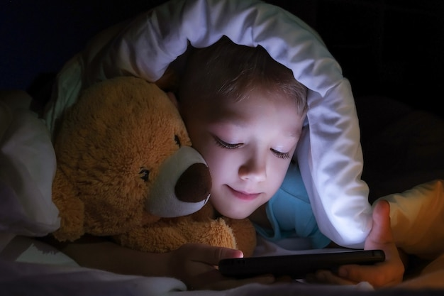 Szczęśliwy chłopiec leży z zabawkowym misiem w łóżku pod kocem i korzysta z urządzenia smartphone cyfrowy tablet w ciemności.