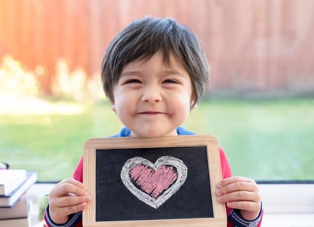 Szczęśliwy chłopiec mienia łupkowy blackboard z rysunkowym różowym i białym sercem