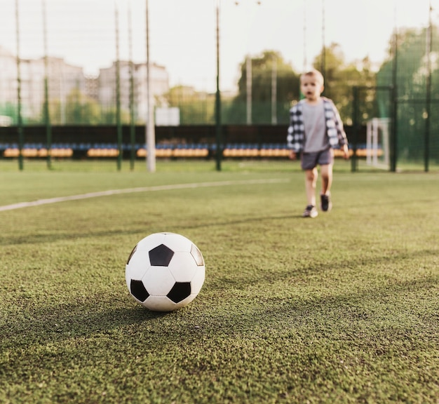 Szczęśliwy chłopiec na zewnątrz gry w piłkę nożną